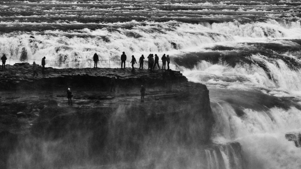 Tourists on an outcrop of rock at the head of the Gullfoss waterfall